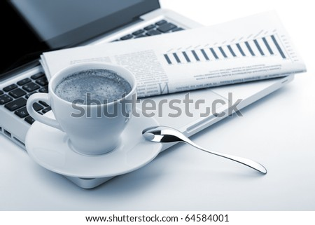 Cappuccino cup with laptop and newspaper. Blue toned