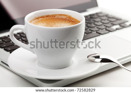 Cappuccino cup with spoon on laptop. Small DOF - stock photo