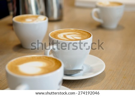 cappuccino cups on the brown wooden table - stock photo