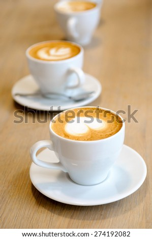 cappuccino cups on the brown wooden table