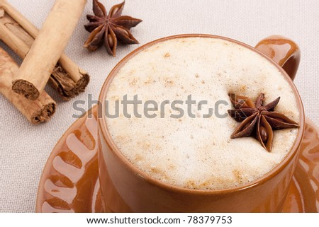 Cappuccino in a brown ceramic cup with spice.