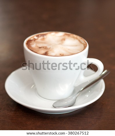 Cappuccino in a white cup on the table.