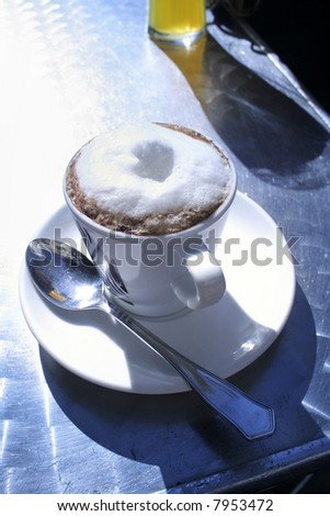 Cappuccino on sunny table - stock photo