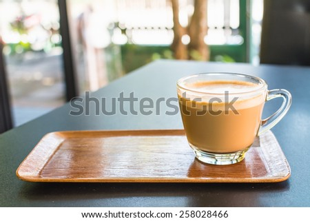 Cappuccino or latte coffee in a clear glass mug on wooden tray. - stock photo