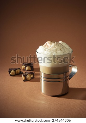Cappuccino  with chocolate and hazelnuts isolated on brown - stock photo