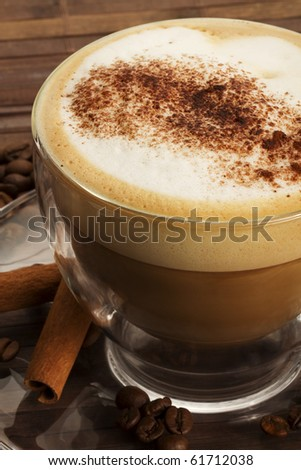 cappuccino with chocolate powder on milk froth and cinnamon sticks on wooden background - stock photo