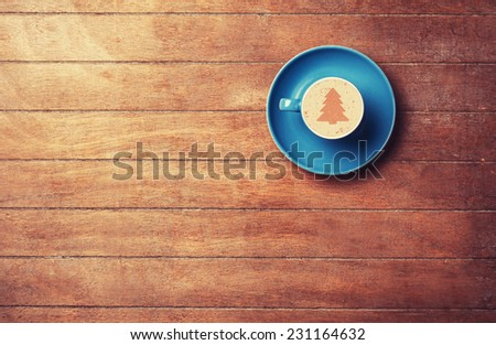 Cappuccino with christmas tree shape on a wooden table. - stock photo