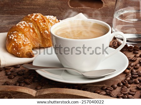 Cappuccino with croissant and glass of water in the tray of brown wood. - stock photo