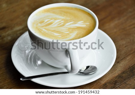 Cappucino coffee cup on wooden table - stock photo