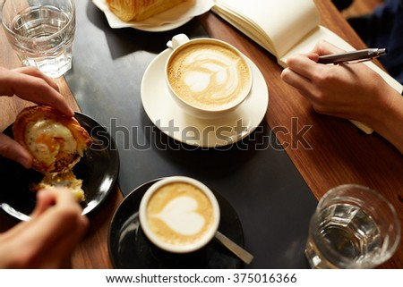 Cappucino, espresso, pastry and a hand taking notes - stock photo
