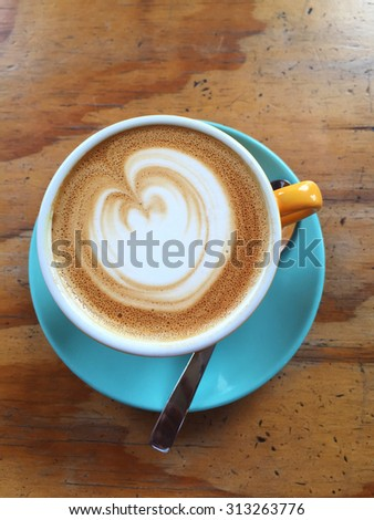 cappucino or flat white coffee served in a yellow cup and pastel blue saucer . Has a rustic wooden background  - stock photo