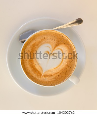 Cappucino with heart shape foam on white saucer with spoon - stock photo