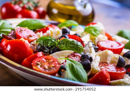 Caprese Italian or Mediterranean salad. Tomato mozzarella basil leaves black olives and olive oil on wooden table.