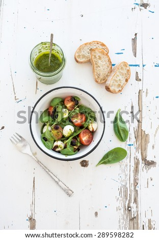 Caprese salad and chiabatta slices. Cherry-tomatoes, baby spinach and mozzarella in metal bowl with pesto dressing on rustic white wooden backdrop, top view, - stock photo