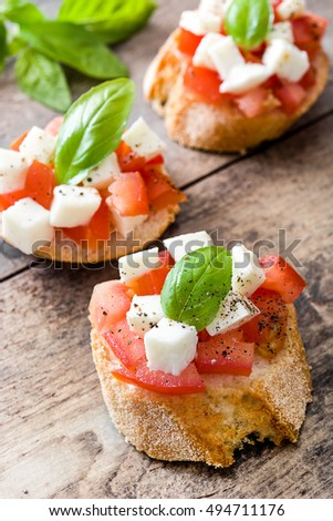 Caprese salad bruschettas on wooden table