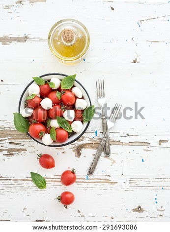 Caprese salad: cherry-tomatoes and mozzarella in metal bowl with olive oil on rustic white wooden backdrop, top view, copy space - stock photo