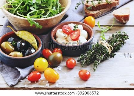 Caprese salad ingredients : arugula, mozzarella cheese ,olives and tomatoes.Selective focus - stock photo