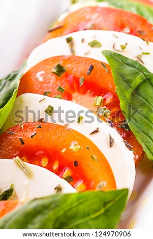 Caprese salad: slices of tomato and mozzarella cheese - stock photo