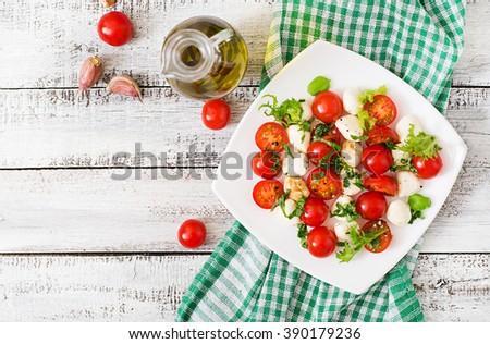 Caprese salad tomato and mozzarella with basil and herbs on a white plate. Top view - stock photo