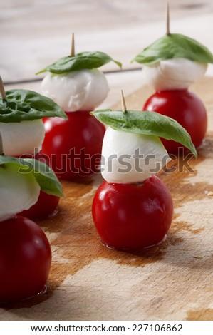 Caprese salad, typical Italian appetizer with mozzarella cheese, tomato, basil, oil, oregano - stock photo