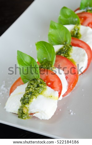 Caprese Salad,Vine ripeTomato and Mozzarella slices with basil leaves and fresh green pesto.