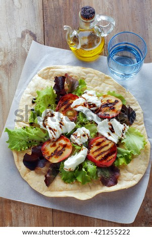 Caprese salad with fresh lettuce, mozzarella cheese and peaches on the grill. with flatread. healthy snack. comfort street food - stock photo