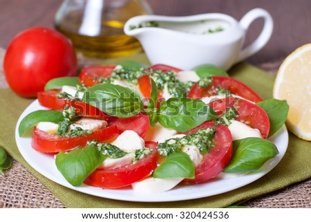 Caprese salad with ingredients like oil, tomatoes and mozzarella cheese - stock photo