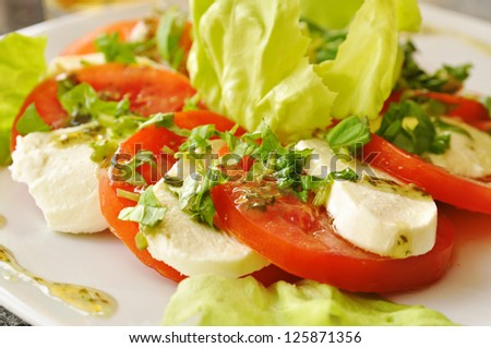 Caprese salad with mozzarella cheese, tomatoes and green lettuce in restaurant - stock photo