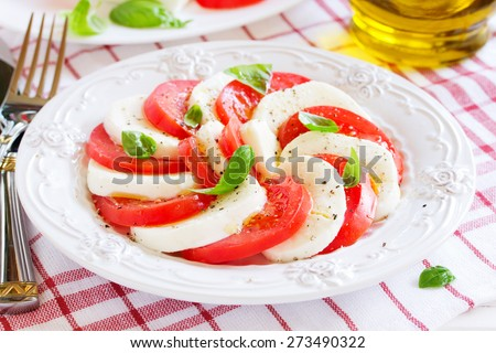 Caprese salad with tomatoes, mozzarella and basil. - stock photo