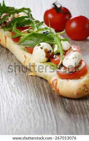 Caprese sandwich of mozzarella cheese, tomato and basil - stock photo
