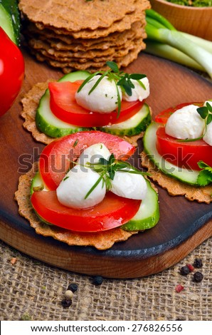 Caprese sandwiches of mozzarella cheese, tomato, cucumber and thyme on the desk  - stock photo