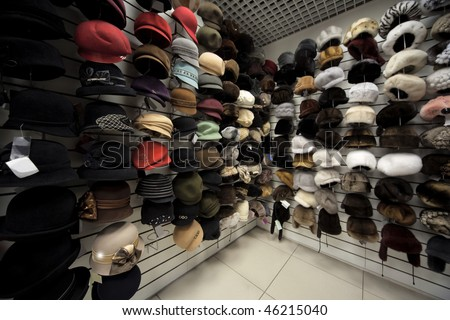 Caps, winter caps, hats, berets and other headdress on wall in shop - stock photo
