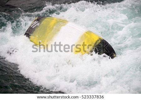 Capsized kayak boat on rough water