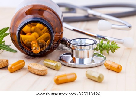 capsule of herbal medicine alternative healthy care with stethoscope wooden background. - stock photo