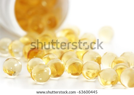 Capsules of fish oil spilled out open container on white background. - stock photo