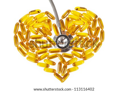 Capsules of fish oil with stethoscope. Shot in studio - stock photo