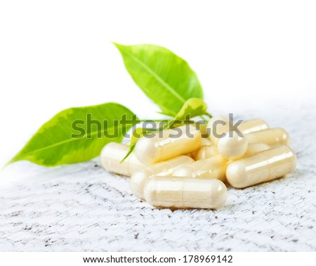 Capsules on white wooden background. - stock photo