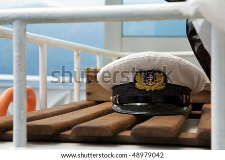 Captains cap on board on a wooden bench - stock photo