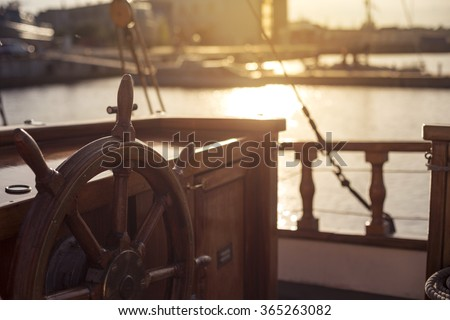 Captains steering wheel of an old wooden sailing ship in a port at sunset - stock photo