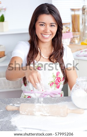 Captivating asian woman baking in her kitchen smiling at the camera - stock photo