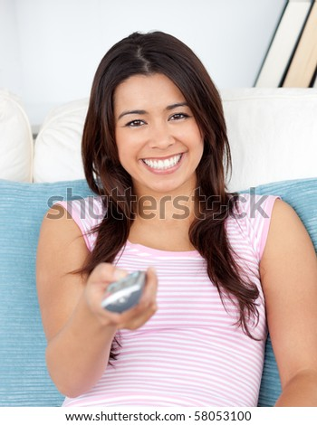 Captivating asian woman holding a remote smiling at the camera sitting in the living room - stock photo