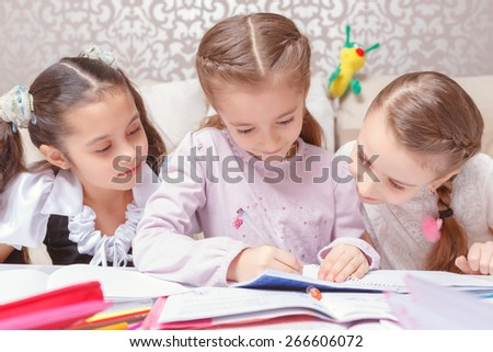 Captivating world of science. Closeup of three small schoolgirls leaning forward during reading a book at home - stock photo
