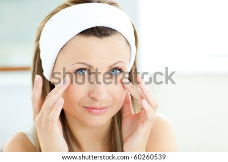 Captivating young woman using cream wearing a bath robe in the bathroom at home - stock photo