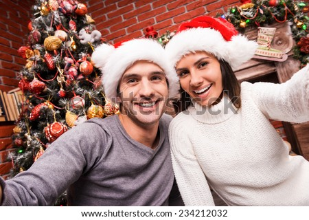 Capturing a happy moment. Beautiful young loving couple bonding to each other and smiling while making selfie with Christmas Tree in the background  - stock photo