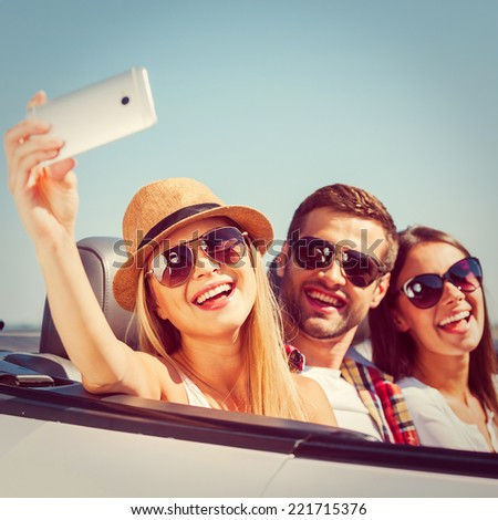 Capturing a moment. Three young happy people enjoying road trip in their white convertible and making selfie - stock photo