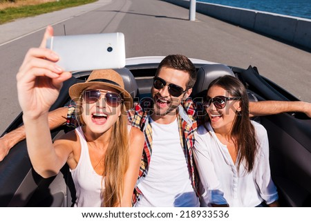 Capturing bright moments. Top view of three young happy people enjoying road trip in convertible and making selfie - stock photo