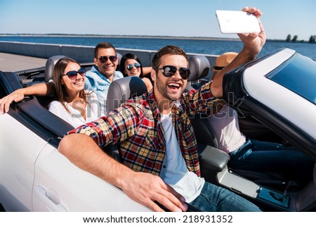 Capturing fun. Group of young happy people enjoying road trip in convertible and making selfie - stock photo
