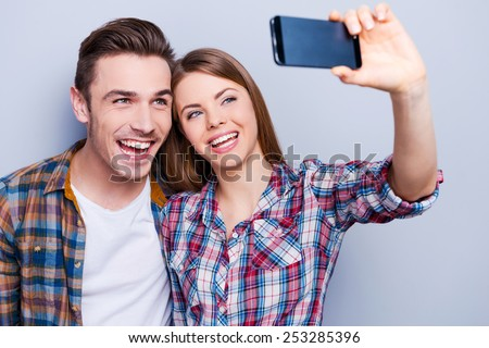 Capturing happy moments together.  Happy young loving couple making selfie and smiling while standing against grey background - stock photo