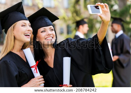 Capturing happy moments. Two happy women in graduation gowns making selfie and smiling while two men standing in the background  - stock photo