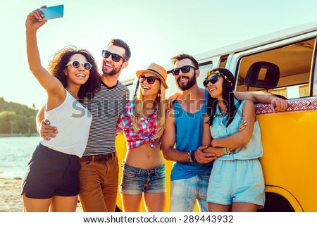 Capturing summer fun. Group of happy young people bonding to each other and making selfie while standing near their retro mini van - stock photo